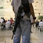 Man with books and a gun at the Kotel_fin