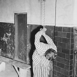 A prisoner reenacts a torture pose in the prison of the Dachau concentration camp