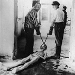 Survivors of the Dachau concentration camp demonstrate the operation of the crematorium by dragging a corpse toward one of the ovens. Dachau, Germany, April 29-May 10, 1945