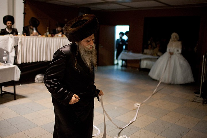 Jewish Bride holds a strip of cloth attached to the father of the groom