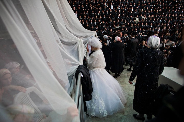 A bride looks into the women's section during traditional Jewish wedding